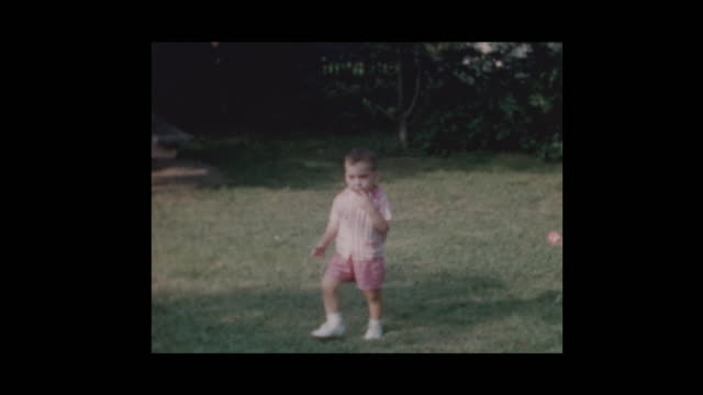 1960 cute toddler boy in pink outfit wandering around - hotel reception filmów i materiałów b-roll