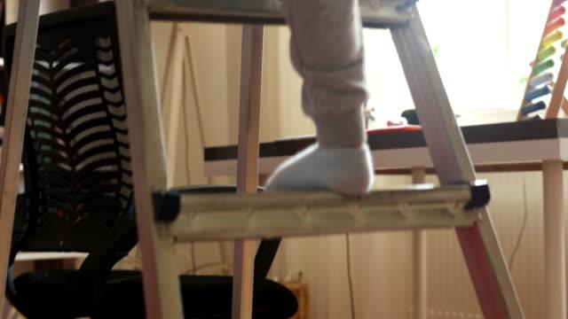 cute toddler boy is climbing the stairways at home. - niebezpieczeństwo filmów i materiałów b-roll