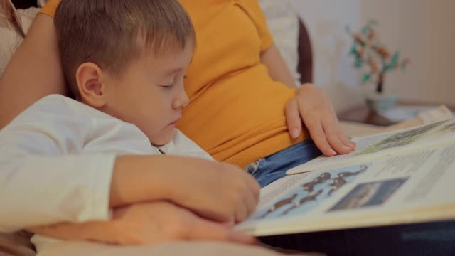 söt liten knatte pojke läsebok med mamma innan du går att sova - cosy pillows mother child bildbanksvideor och videomaterial från bakom kulisserna