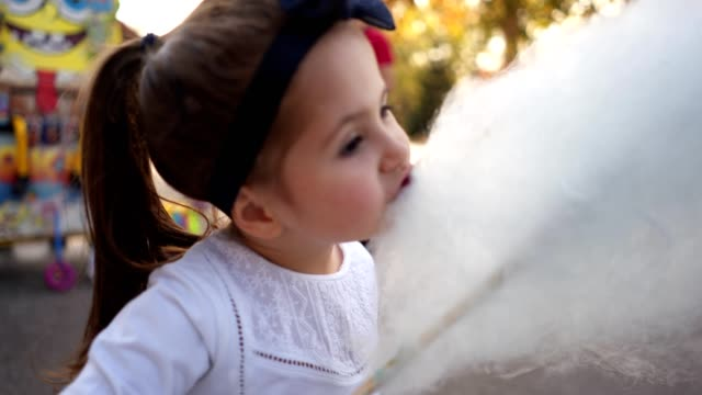 Cute toddler eating cotton candy in a park Cute toddler girl enjoying a cotton candy snack outdoors in a city park. cotton candy stock videos & royalty-free footage