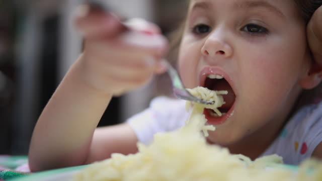 vidéos et rushes de mignon bébé manger des spaghettis à la maison avec une fourchette - spaghetti bolognaise