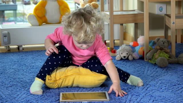 stockvideo's en b-roll-footage met schattig peuter meisje gebruik tablet pc zittend op blauw tapijt. gelukkige kind klappen handen - blond curly hair