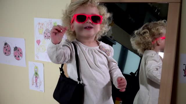 stockvideo's en b-roll-footage met schattig peuter meisje met roze zonnebril en handtas poseren in de voorkant van de spiegel - blond curly hair