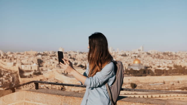 Cute tourist girl talks on video call. Jerusalem Israel. Pretty European traveler woman smiling happy and excited. 4K video