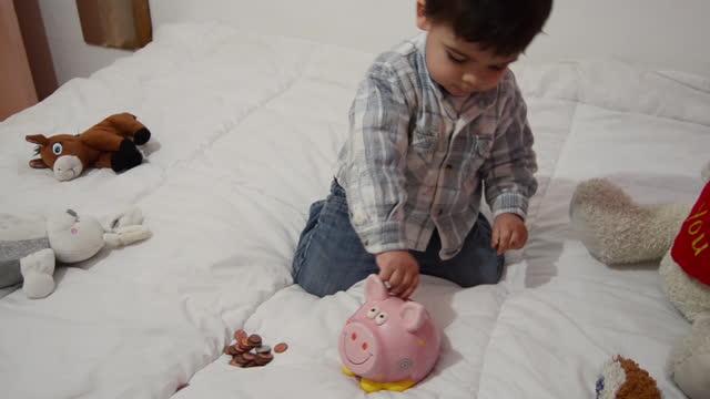 vidéos et rushes de mignon deux ans bébé garçon jouant avec tirelire et mettant des pièces à l'intérieur - tirelire