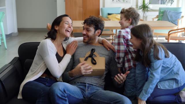 vídeos de stock, filmes e b-roll de mulher bonito e caçoa o homem surprising que senta-se no sofá com o smartphone com um presente do dia de pai - fathers day