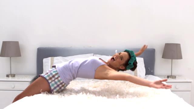 ładny kobieta spadające na jej łóżko - kołdra filmów i materiałów b-roll