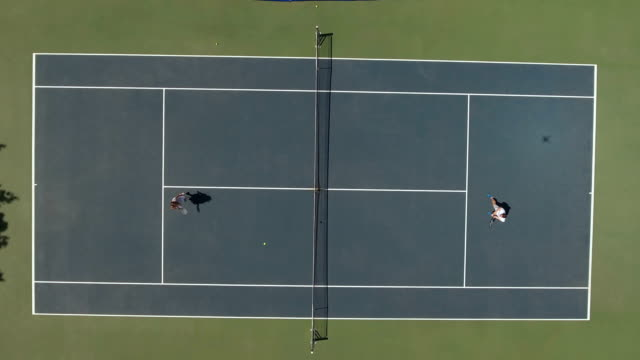 Cute woman in dress and young guy in shorts play tennis at the court video