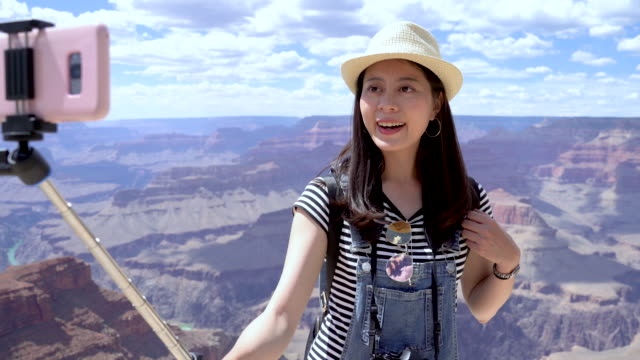 cute woman in overalls hiking in grand canyon young girl travel student holding selfie stick with cellphone on it take self portrait in camera app. beautiful lady using smartphone technology concept. cute woman in overalls hiking in grand canyon canyon stock videos & royalty-free footage