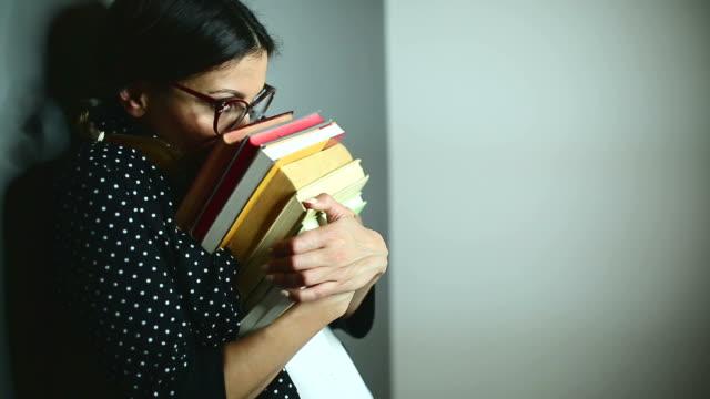 Cute woman peeking behind books, changing emotions video