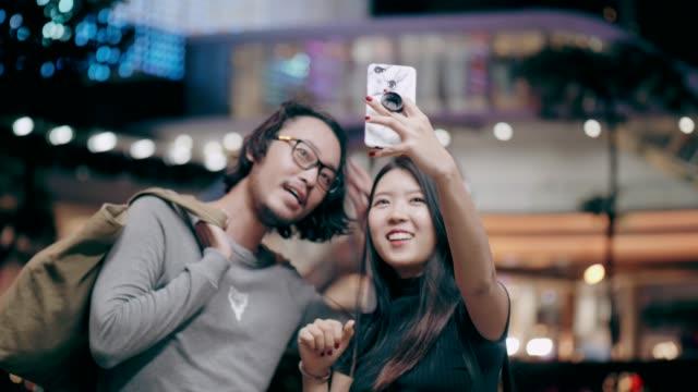 şehirde seyahat ederken sevimli kadın selfie - flört etmek stok videoları ve detay görüntü çekimi
