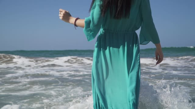 Cute woman with a perfect body wearing turquoise dress enjoys sea waves standing in the water. The wave rolls on a girl in a light summer dress and gives her a lot of pleasure.