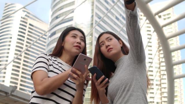 söt ung asiatisk kvinna resenär används smart telefon medan du går på urban trottoaren. - walking home sunset street bildbanksvideor och videomaterial från bakom kulisserna