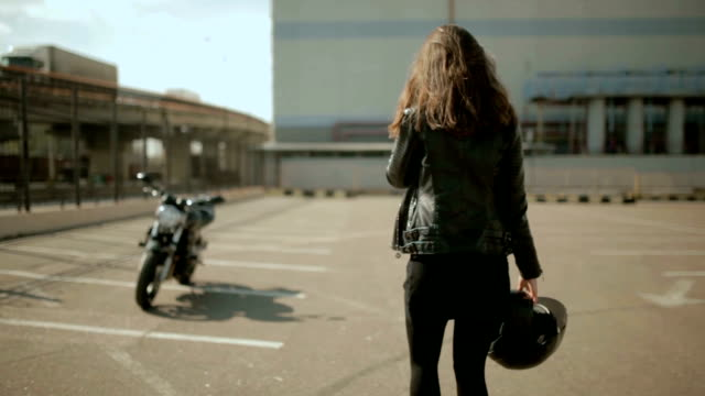 Cute young brunette woman and motorcycle on street Cute young brunette woman and motorcycle on street of Odessa crash helmet stock videos & royalty-free footage