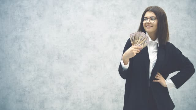 cute young businesswoman in formal suit, her hand akimbo, waving a fan of money banknotes near her face, making wind. it is too hot. - mani sui fianchi video stock e b–roll