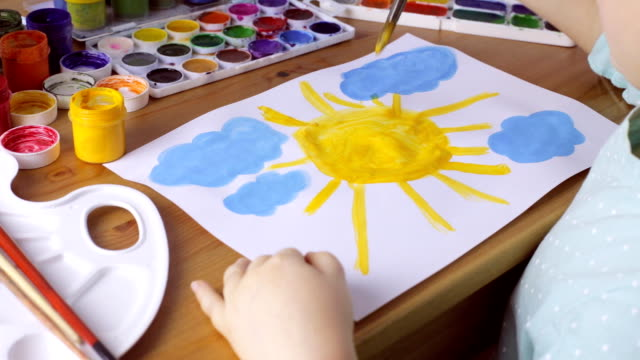 Cute young girl draws yellow sun and blue clouds. Painting concept
