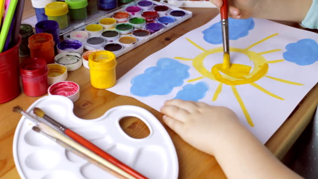 Cute young girl draws yellow sun on white paper