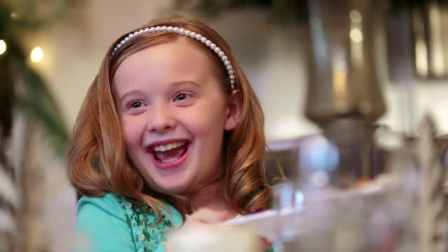stockvideo's en b-roll-footage met cute young girl helps pass plates of food around table for christmas dinner - omgeving