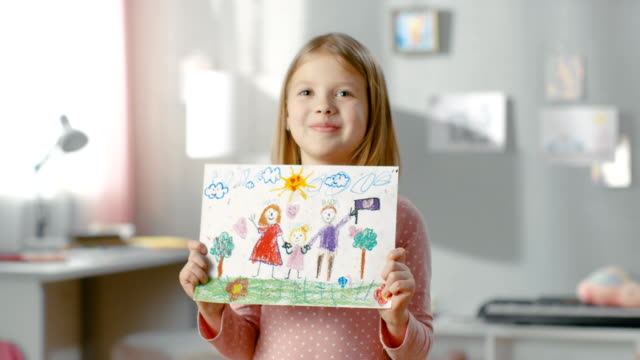 cute young girl shows fun drawing of her happy family. mother, father and her holding hands on the drawing. - matita colorata video stock e b–roll