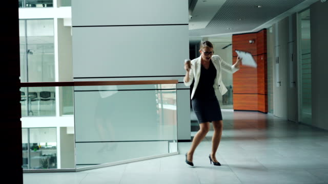 Cute young lady manager is dancing in hall of business center holding documents and take away coffee enjoying freedom at lunch break. Work and fun concept.