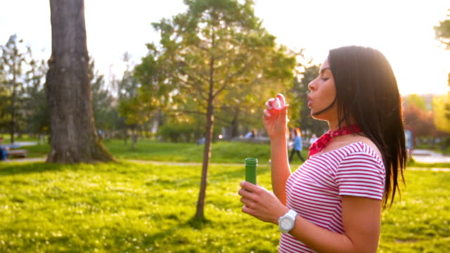Cute young woman blowing bubbles video