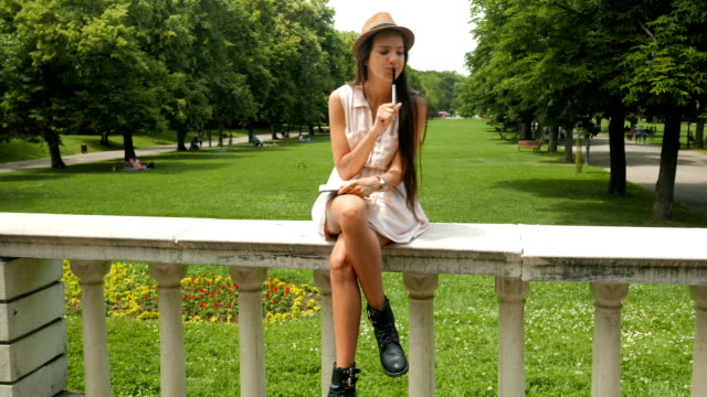 Cute young woman hand writing in her diary or notebook outdoors video
