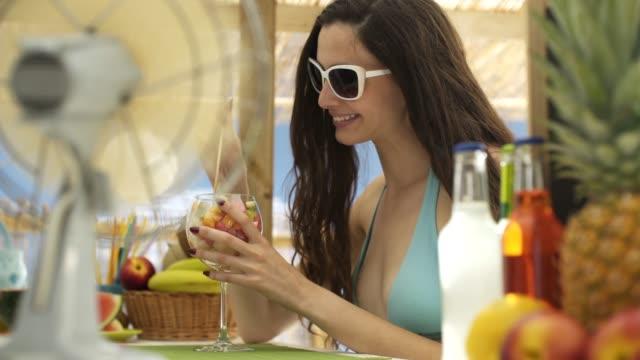 vídeos de stock, filmes e b-roll de mulher nova bonito que tem uma salada de fruta na barra de praia - fruit salad