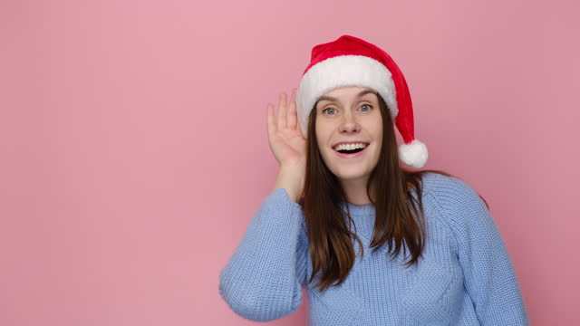 Cute young woman in Christmas red hat try to hear you overhear listening intently, dressed in cozy blue sweater, isolated on pink background studio. Happy New Year celebration merry holiday concept