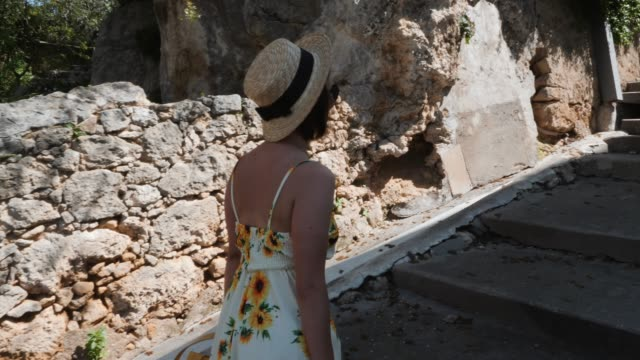 Cute young woman in summer dress and straw hat with sunglasses climbing steps with beautiful architecture and smiling