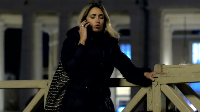 cute young woman is having conversation with mobile phone in the evening video