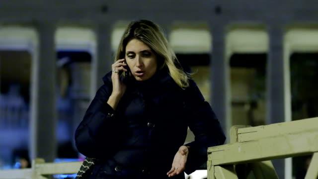 sevimli genç kadın akşam akıllı cep telefonu ile sohbet ediyor - vatikan şehir devleti stok videoları ve detay görüntü çekimi