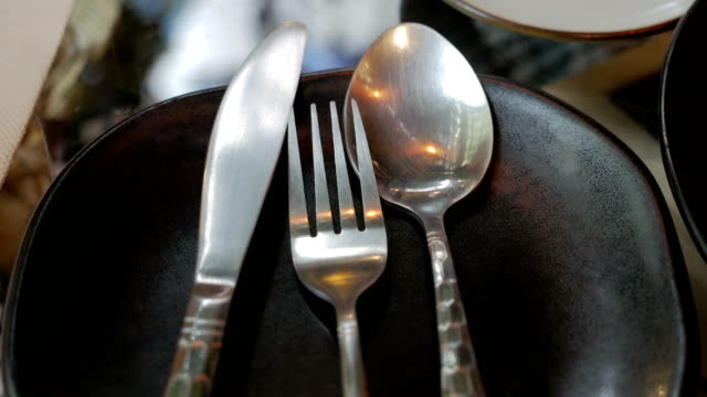 cutlery set of spoon and fork and knife on black plate video