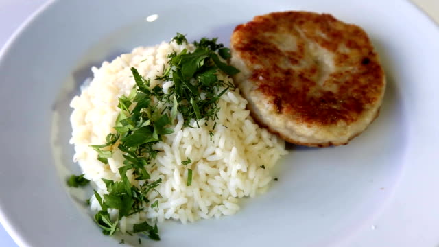 Cutlet with rice and greens on a rotating white plate video