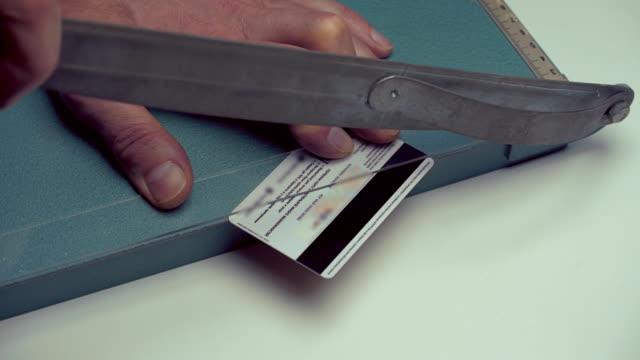 cutter cuts a credit card in half - credit card стоковые видео и кадры b-roll