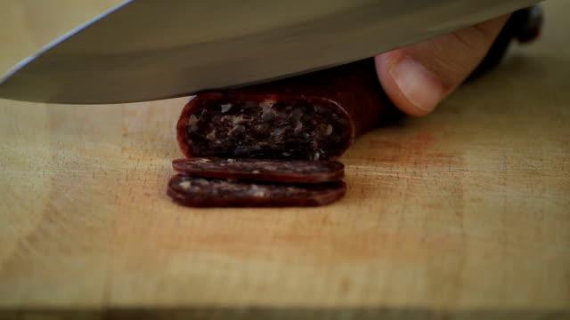 Cuttin air-dried sausage called sudzhuk Closeup of cutting bulgarian traditional flat sausage called sudzhuk. jerky stock videos & royalty-free footage