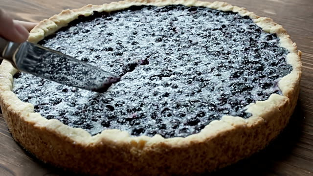 Cutting a blueberry pie into pieces Cutting a blueberry pie into pieces, on the wood table, close up painting art product stock videos & royalty-free footage