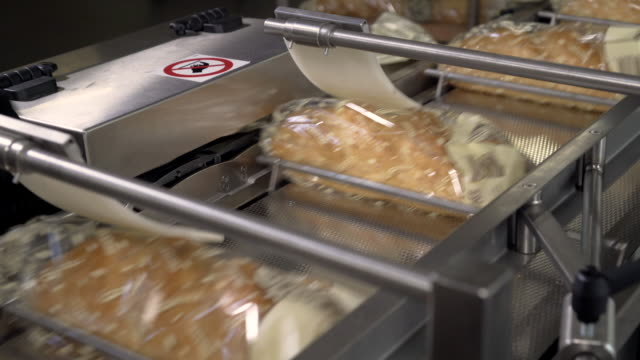 Cutting a loaf of bread into pieces and packing it into bags. Machine for cutting bread. Sliced bread in the factory. Manufacturing process. Bread Slice Automatic Machine