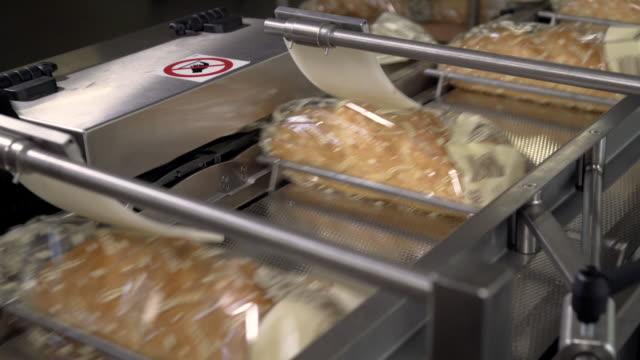 Einen Laib Brot in Stücke schneiden und in Säcke packen. Maschine zum Brotschneiden. In der Fabrik geschnittenes Brot. Herstellungsprozess. Brotscheibe Automatik – Video