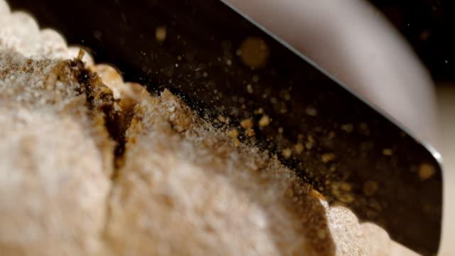 SLO MO CU Cutting a piece of bread