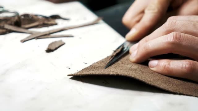 vídeos y material grabado en eventos de stock de corte un pedazo de cuero con cuchillo - piel textil
