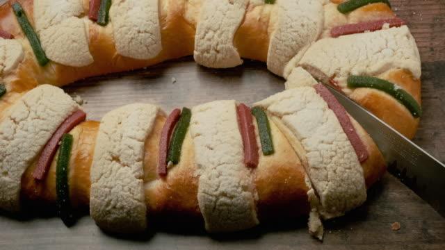 vidéos et rushes de couper un rosca roscon de reyes (gâteau d'épiphanie latino-américain) - galette des rois