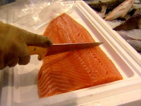 Cutting a salmon at the fish market. video