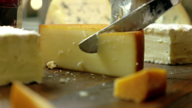 Cutting a Serving from the Cheese Closeup shot of a piece of cheese. Somebody is cutting a serving of it with a knife. cheese stock videos & royalty-free footage