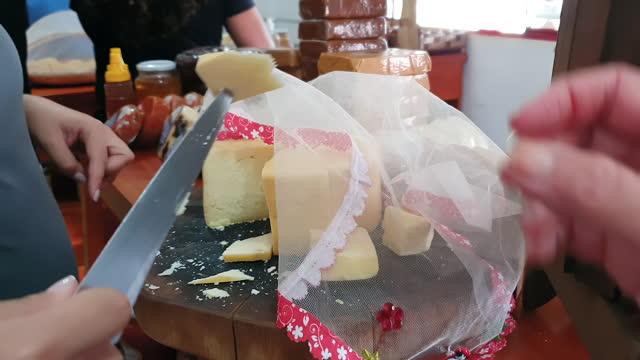 mağaza müşterisinin tatması için bir dilim peynir kesme - minas gerais eyaleti stok videoları ve detay görüntü çekimi