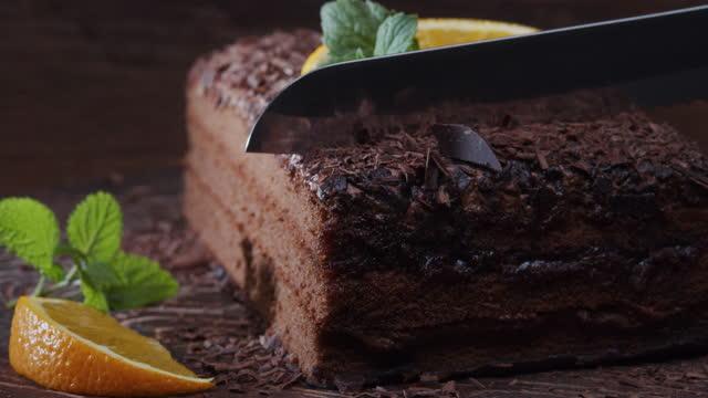 taze portakal ve nane ile süslenmiş çikolatalı kek bir dilim kesme. aşırı yakın çekim - kek dilimi stok videoları ve detay görüntü çekimi