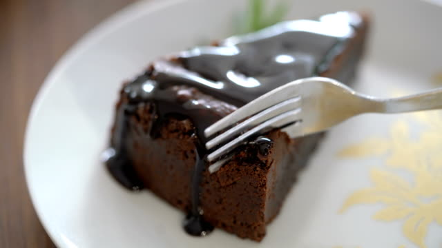 4k cutting a slice of chocolate cake with folk - desserts stock videos and b-roll footage