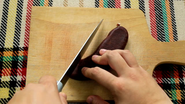 Cutting air-dried sausage. First person view. Cutting bulgarian traditional flat sausage called sudzhuk. First person point of view concept. jerky stock videos & royalty-free footage