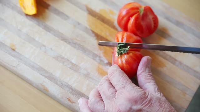 vidéos et rushes de couper un agrandi de tomates de variétés anciennes - lame