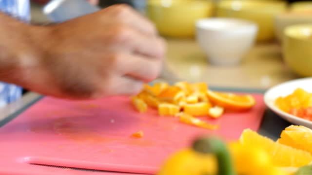 schneiden eine orange auf ein schneidebrett mit einem scharfen messer - amerikanische geldmünze stock-videos und b-roll-filmmaterial