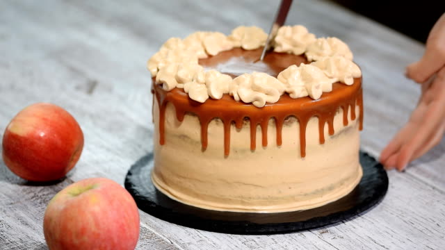 Cutting apple cake with spices, cinnamon, dried apples, creamy caramel in autumn style.